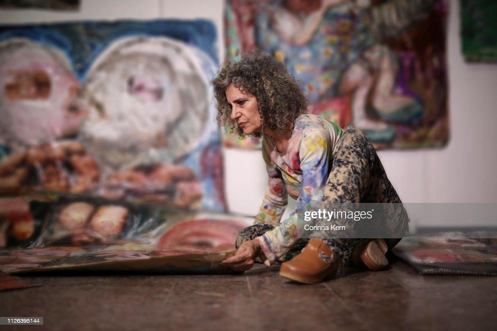 Woman arranging her artwork : Stock-Foto