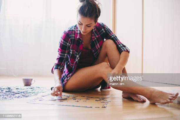 frau arrangiert puzzle zu hause - puzzle stock-fotos und bilder