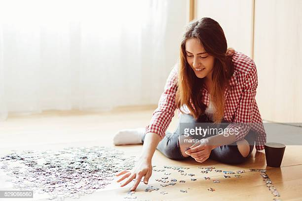 woman arranging jigsaw puzzle at home - raadsel stockfoto's en -beelden
