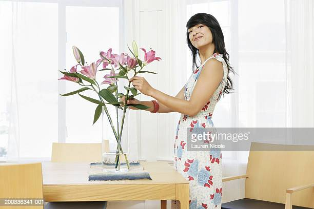 Woman arranging lilies in vase, smiling, side view