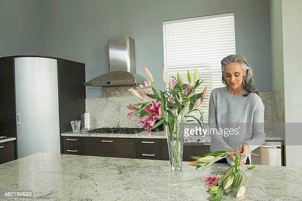 woman arranging lilies - afzuigapparaat stockfoto's en -beelden