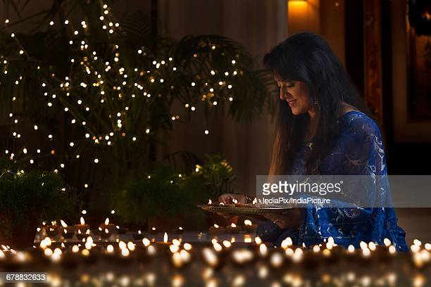 woman arranging oil lamps at a diwali festival - diya oil lamp stock pictures, royalty-free photos & images