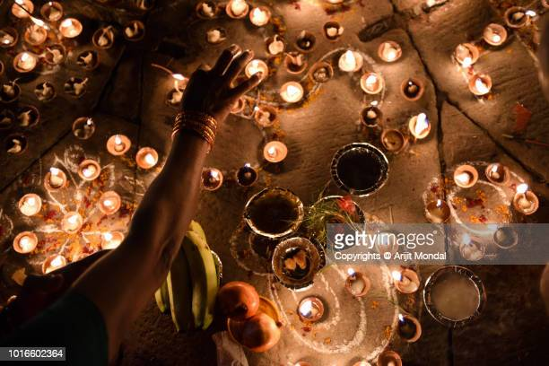woman arranging oil lamps during diwali at ghats of ganga in varanasi, india - ceremony stock pictures, royalty-free photos & images