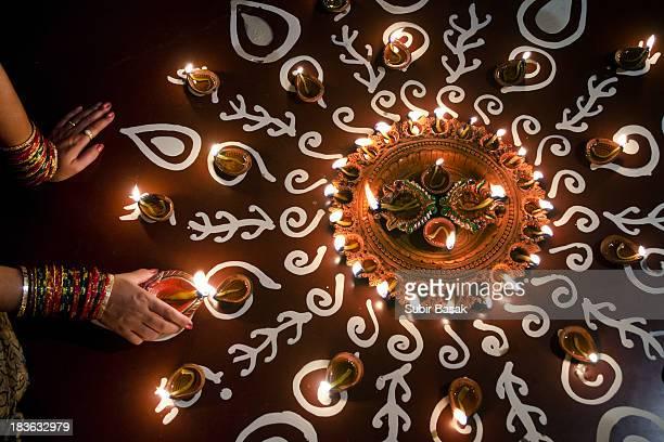 Woman arranging oil lamps on rangoli during Diwali