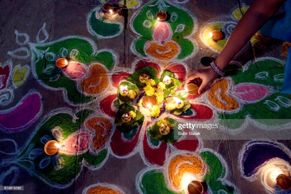 Woman arranging oil lamps on rangoli during Diwali. : Stock Photo