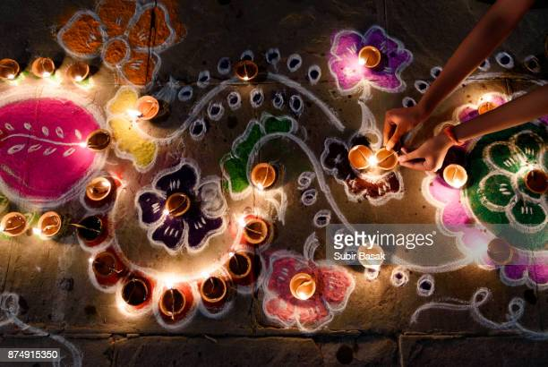 woman arranging oil lamps on rangoli during diwali. - diwali stock photos and pictures
