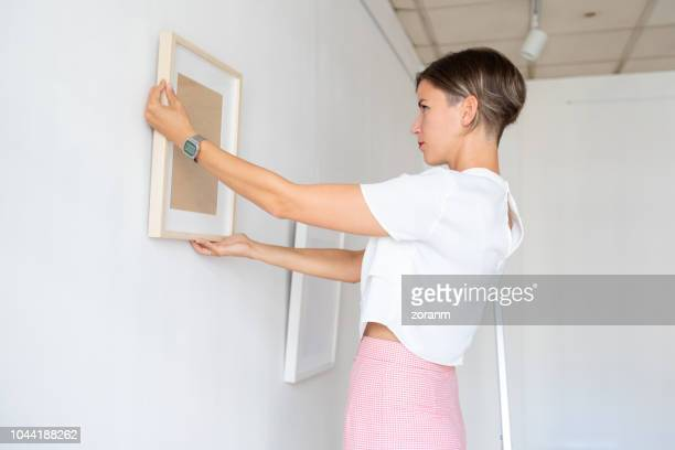 Woman arranging paintings on the wall