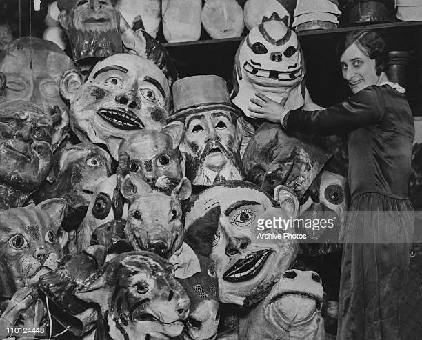 Woman arranging pantomime heads in a store room at a London factory, 11th November 1929. The heads will be used in Christmas pantomimes.