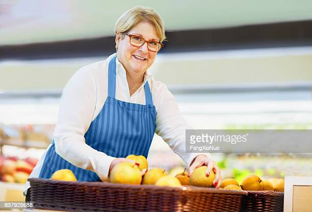 Woman arranging pears at grocery store