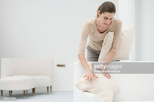 Woman arranging pillows on sofa