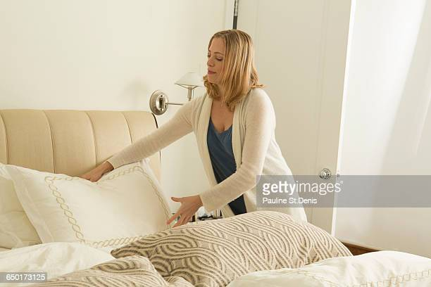 Woman arranging pillows whilst making bed