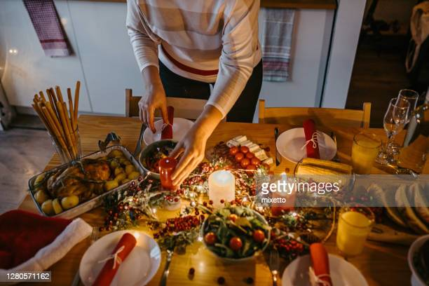 woman arranging table for christmas dinner at home - christmas decore candle stock pictures, royalty-free photos & images