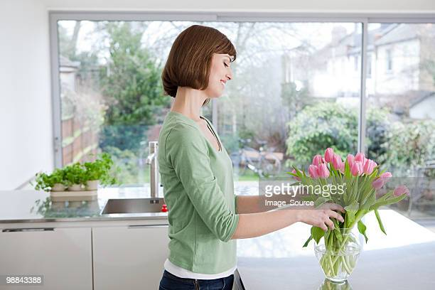 Woman arranging tulips in vase