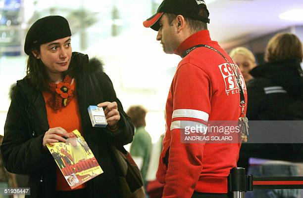 A woman arrives 10 January 2005 with a packet of cigarettes at a cinema in central Rome to watch the Italian premiere of the film 'Nicotina' directed...