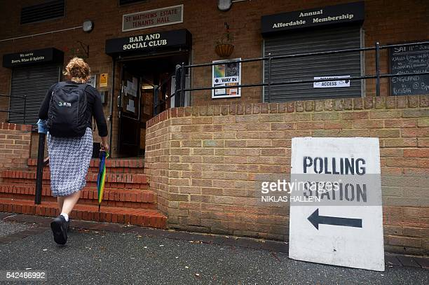 A woman arrives to cast her vote at a polling station in south London on June 23 as Britain holds a referendum on whether to remain in or to leave...