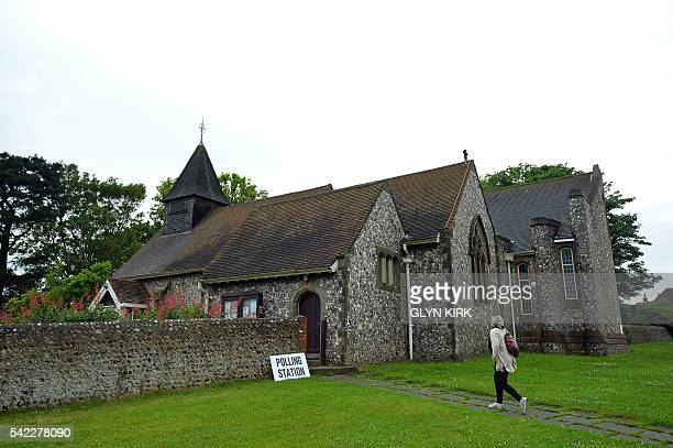 A woman arrives to cast her vote at the Parish church of St Peter in West Blatchington near Brighton in southern England on June 23 as Britain holds...