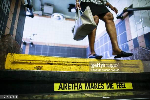 A woman arrives to Franklin Street Subway station while a message for Aretha Franklin is seen on the subway stairs on August 16 2018 in New York New...