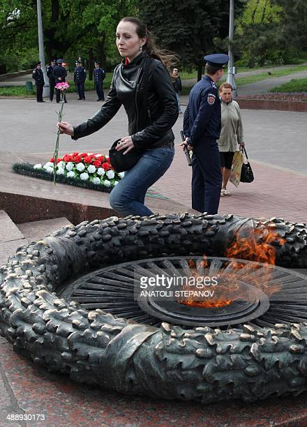 Woman arrives to lay a flower at the Unknown Sailor Memorial on Victory Day in the southern Ukrainian city of Odessa on May 9, 2014. Russian...