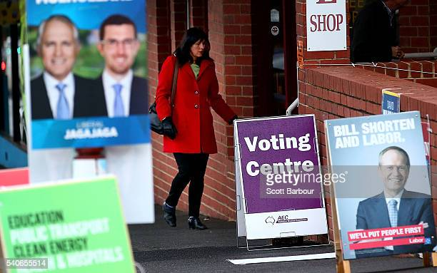 A woman arrives to vote past electoral placards featuring photos of Bill Shorten Leader of the Australian Labor Party and Malcolm Turnbull Leader of...