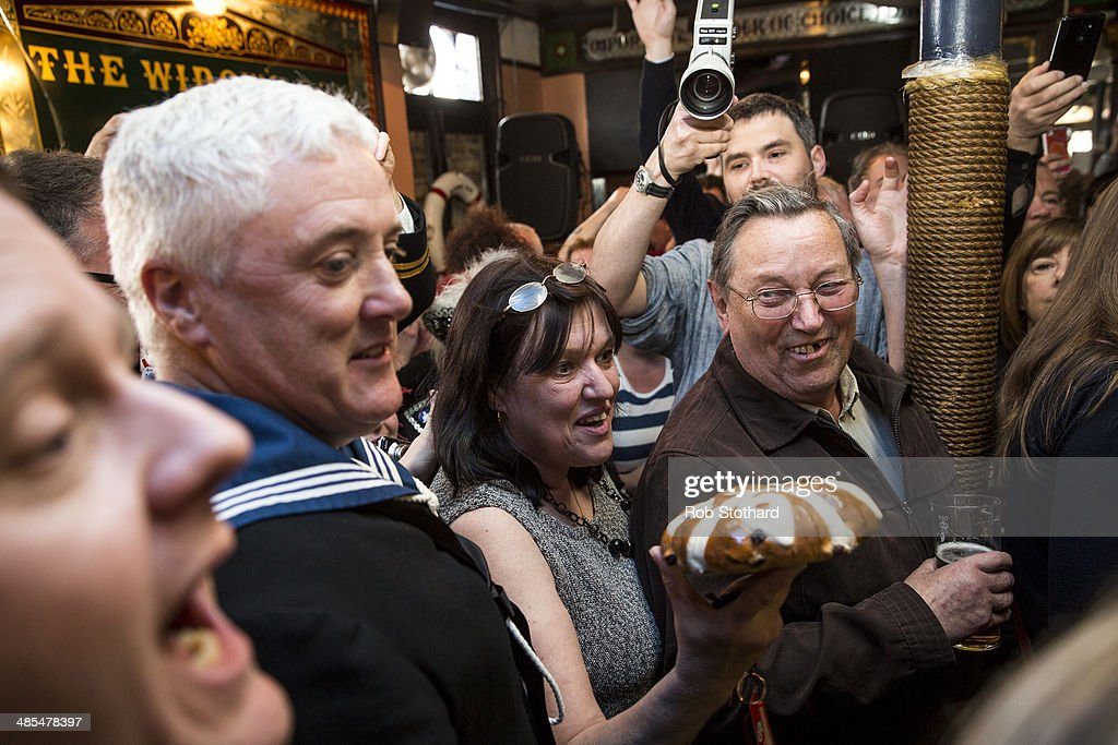 A woman arrives with the 2014 hot cross bun to be hung in a net above the bar of the Widow's Son pub in Bromley-by-Bow on April 18, 2014 in London, England. The Widow's Son was built in 1848 upon the former site of an old widow's cottage who, when her only son left to be a sailor, promised to bake him a Hot Cross Bun and keep it for his return. The son never returned but the widow refused to give up hope, baking a fresh one each year. This annual tradition has been continued in the pub as a remembrance of the widow and her son, and of the bond between all those on land and sea, with sailors of the Royal Navy coming to place the bun in a net above the bar.