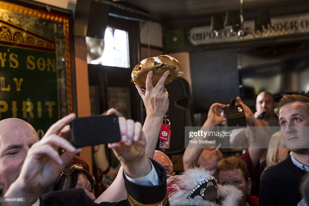 A woman arrives with this year's hot cross bun to be hung in a net above the bar of the Widow's Son pub in Bromley-by-Bow on April 18, 2014 in London, England. The Widow's Son was built in 1848 upon the former site of an old widow's cottage who, when her only son left to be a sailor, promised to bake him a Hot Cross Bun and keep it for his return. The son never returned but the widow refused to give up hope, baking a fresh one each year. This annual tradition has been continued in the pub as a remembrance of the widow and her son, and of the bond between all those on land and sea, with sailors of the Royal Navy coming to place the bun in a net above the bar.