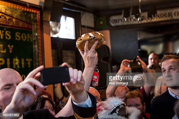 A woman arrives with this year's hot cross bun to be hung in a net above the bar of the Widow's Son pub in BromleybyBow on April 18 2014 in London...