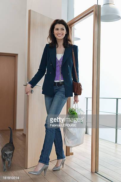 Woman arriving home with a bag of groceries