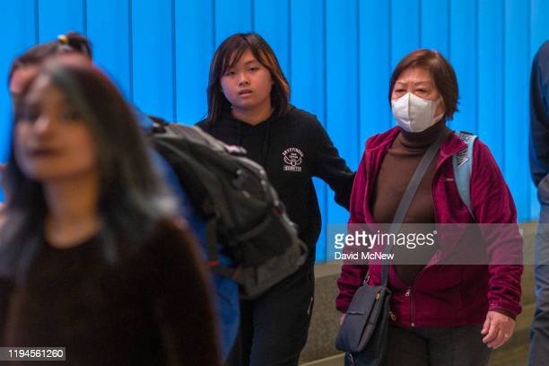 A woman arriving on an international flight to Los Angeles International Airport wears a mask on the first day of health screenings for coronavirus...