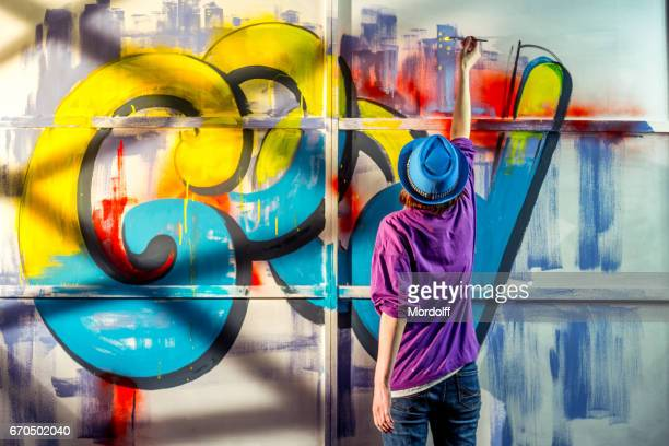 woman artist create graffiti - mural stock pictures, royalty-free photos & images