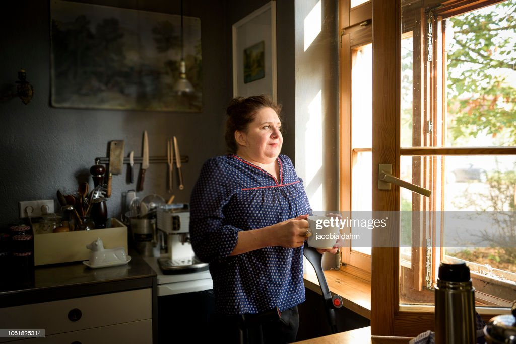 Woman by window, smiling : Stock Photo