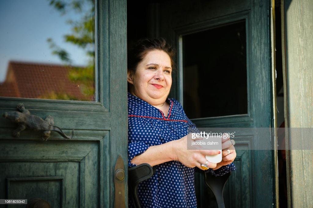 Woman standing in doorway of her home, looking out : Stock Photo