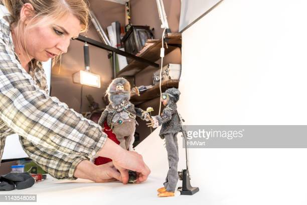 woman artist make stop motion animated video film, frame by frame, using old toys and dresses to adapted in new characters - puppet maker stock pictures, royalty-free photos & images