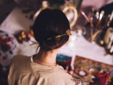 Woman artist working at her studio desk painting - gettyimageskorea