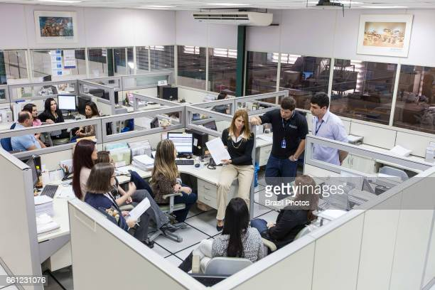 Woman as leader and department boss coordinates her team and gives instructions during office meeting in large industry, Brazil.