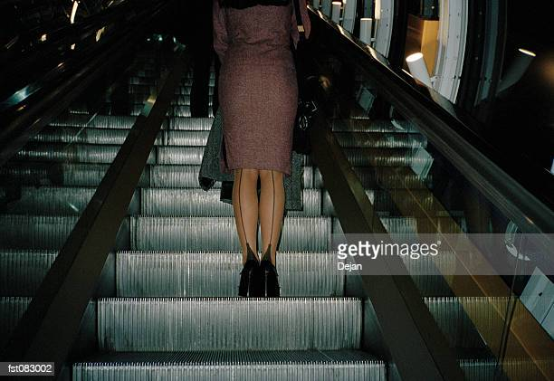 a woman ascending on an escalator - lech stock photos and pictures