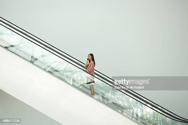 Woman ascending on escalator on hand phone