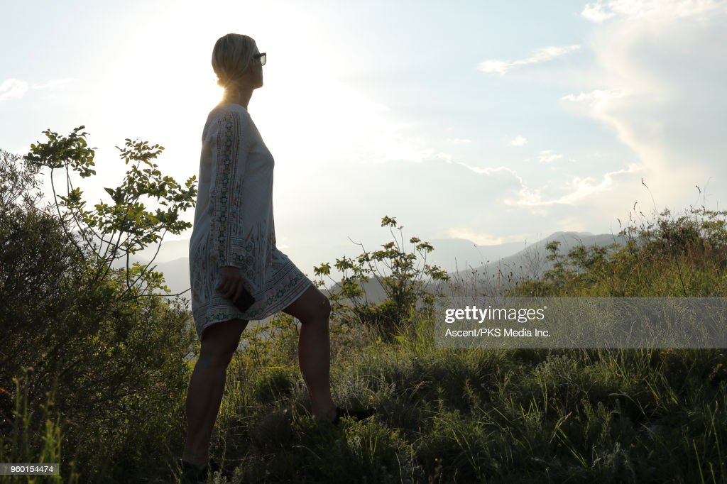 Woman ascends to meadow crest above distant hills : Stock-Foto