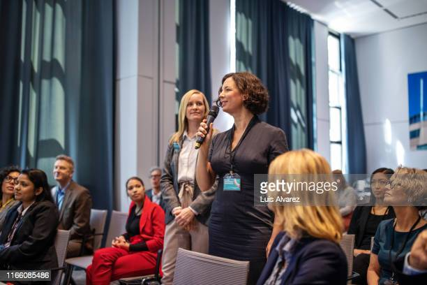 woman asking questions during launch event - q&a stock pictures, royalty-free photos & images