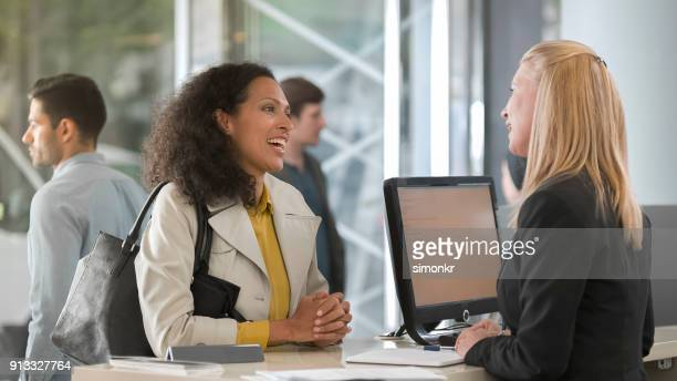 woman asking rental agent for rental car type and female agent helping her - cashier stock pictures, royalty-free photos & images
