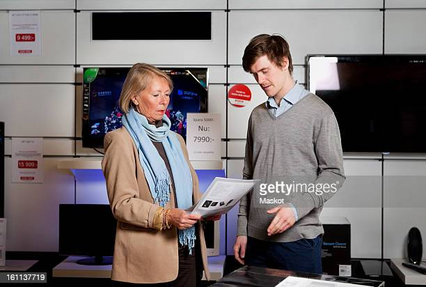Woman asking salesman in TV store