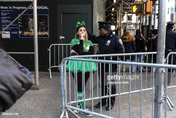 A woman asks a police officer a question during in the annual St Patrick's Day parade along 5th Ave on March 17 2018 in New York City New York's...