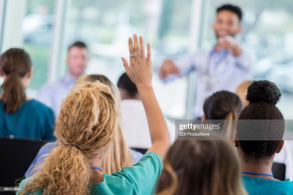 Woman asks question during healthcare seminar : Stock Photo