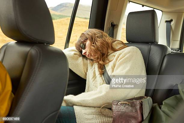Woman asleep in the back of a car