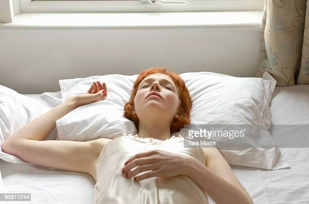woman asleep on bed - lying on back stock pictures, royalty-free photos & images
