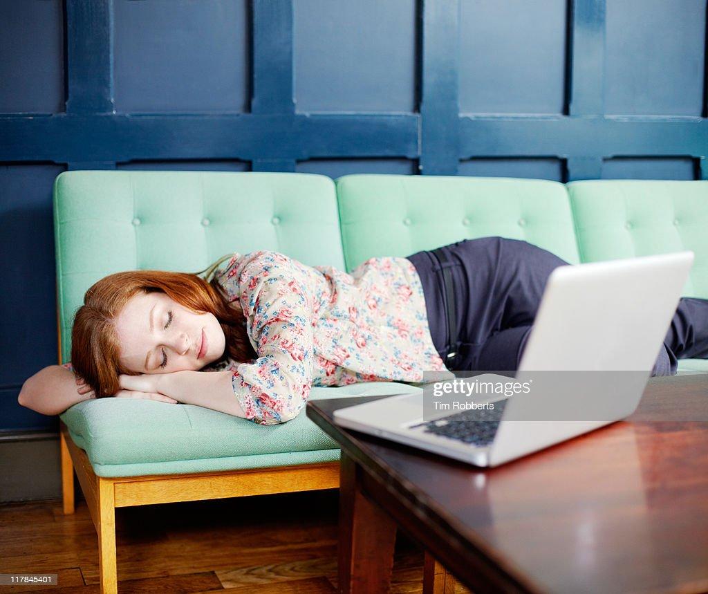 Woman asleep on sofa with laptop : Stock Photo