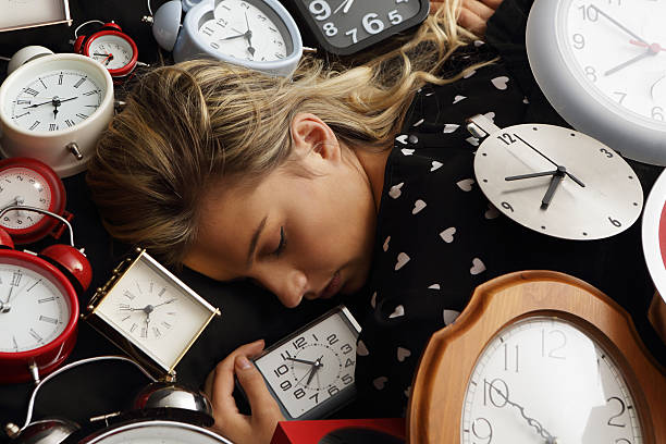woman asleep surrounded by clocks - sleep on your back stock pictures, royalty-free photos & images