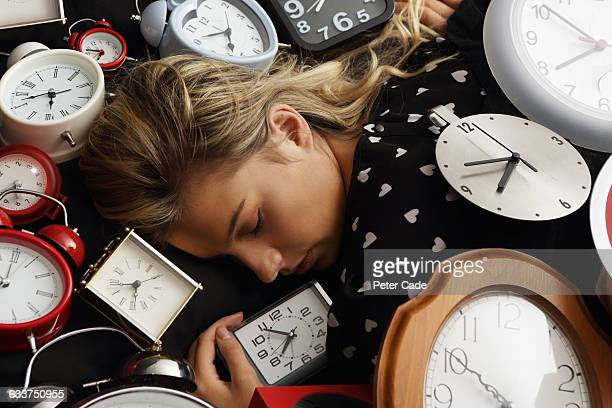 woman asleep surrounded by clocks