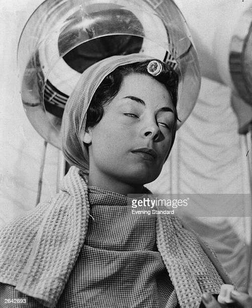 A woman asleep under a hairdresser's hairdryer