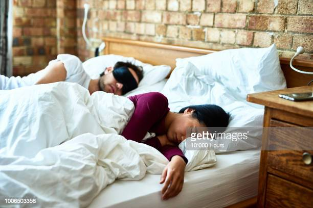 woman asleep with hand on mattress and man wearing eye mask - couple sleeping stock pictures, royalty-free photos & images