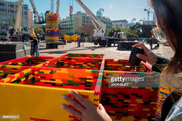 A woman assembles bricks as she works on a component of a LEGO tower under construction in Tel Aviv's Rabin Square on December 26 as the city...